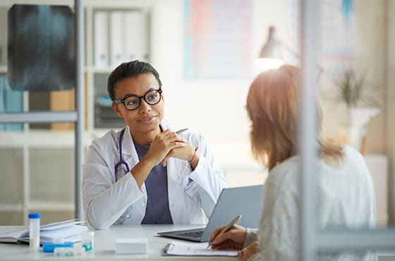 A doctor talks through paperwork with her patient